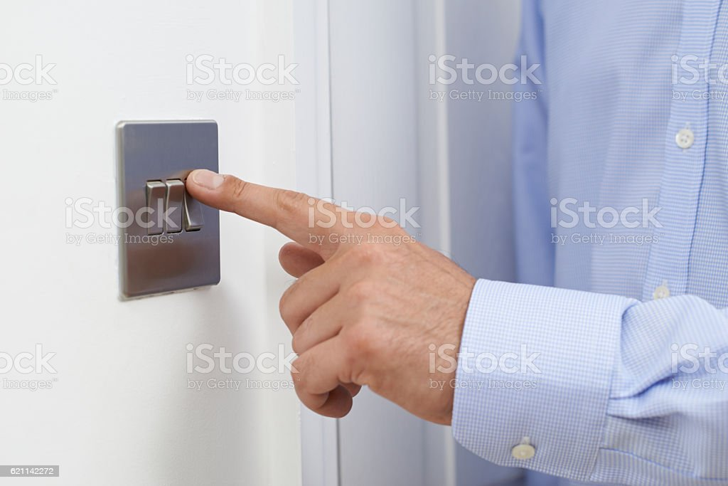Close Up Of Man Turning Off Light Switch stock photo
