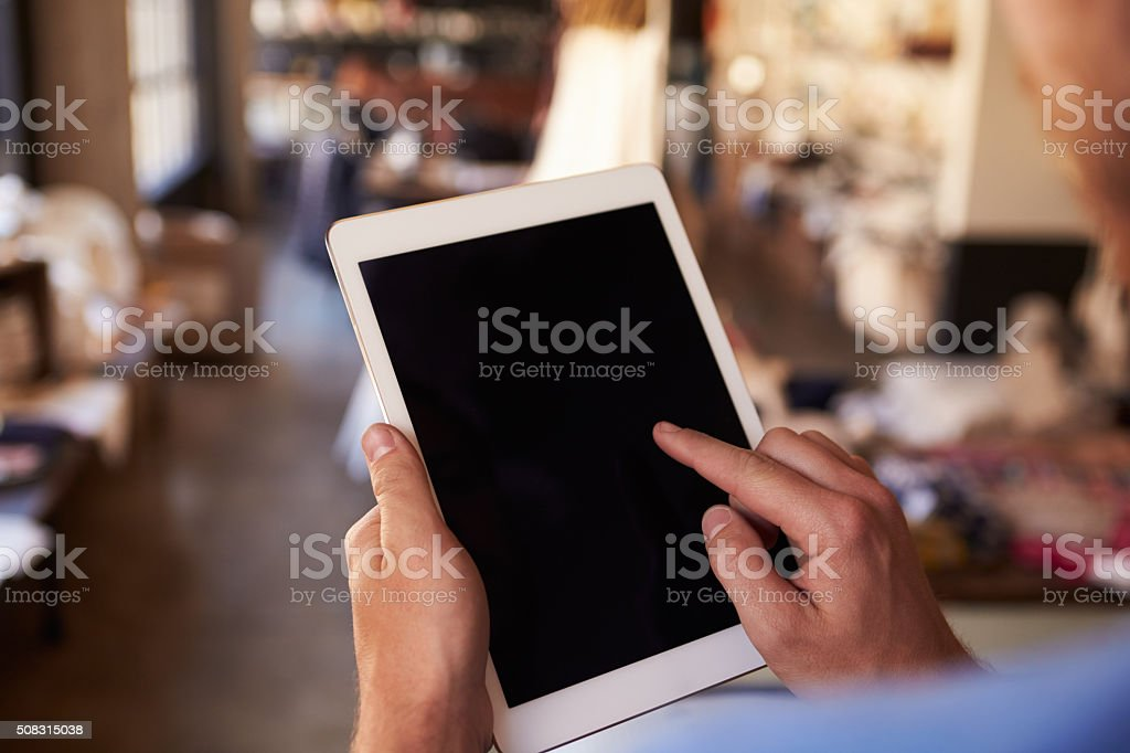 Close Up Of Man Using Digital Tablet In Shop stock photo
