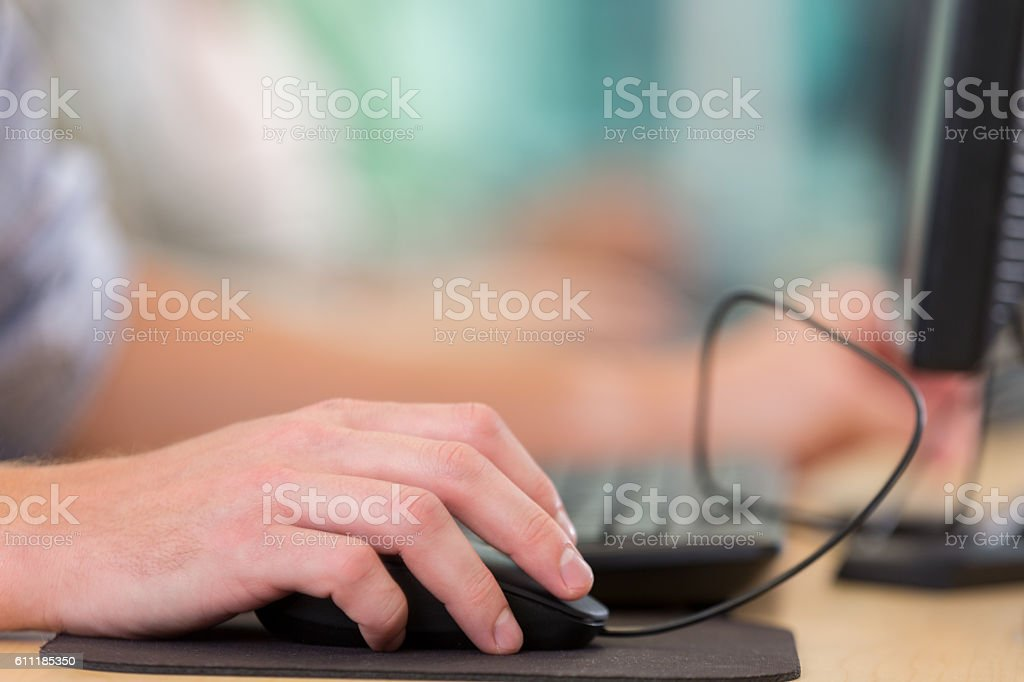 Close up of man using mouse while working stock photo