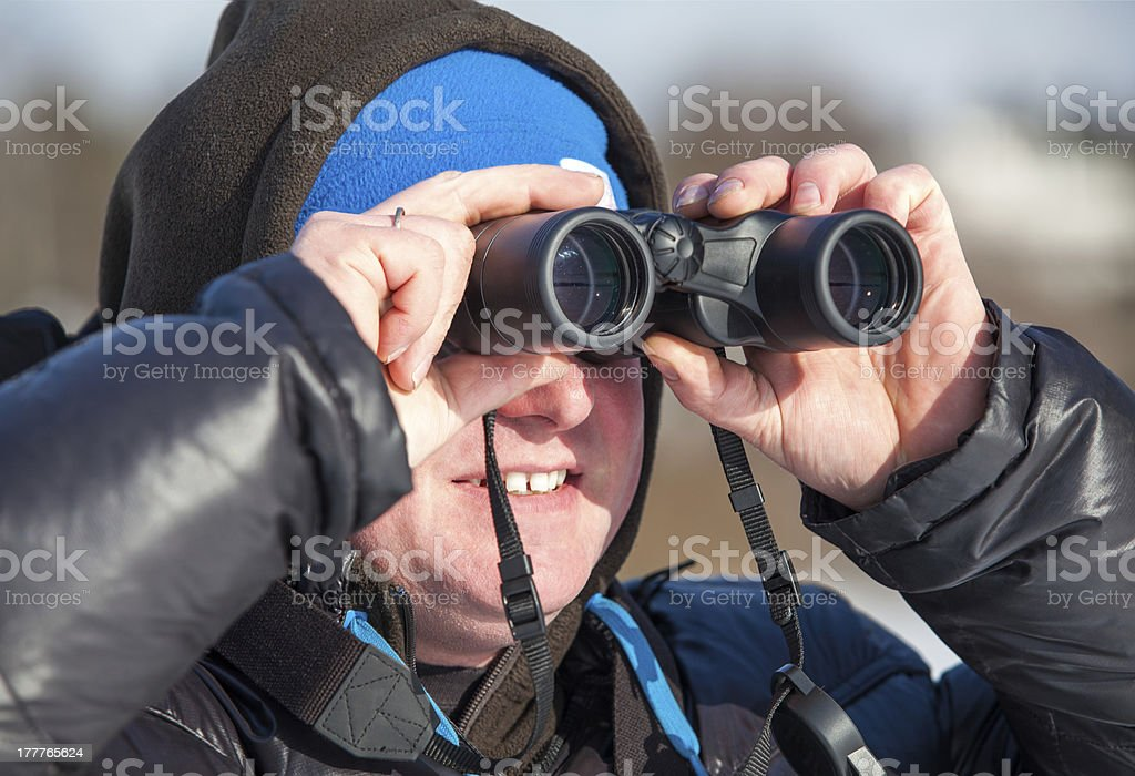 Close up of man with binoculars looking far away royalty-free stock photo