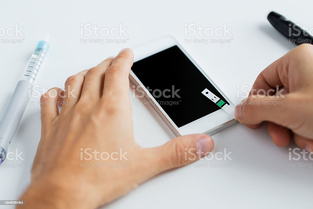 close up of man with smartphone making blood test stock photo
