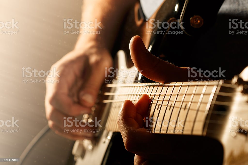 Close up of mans fingers playing electric guitar stock photo