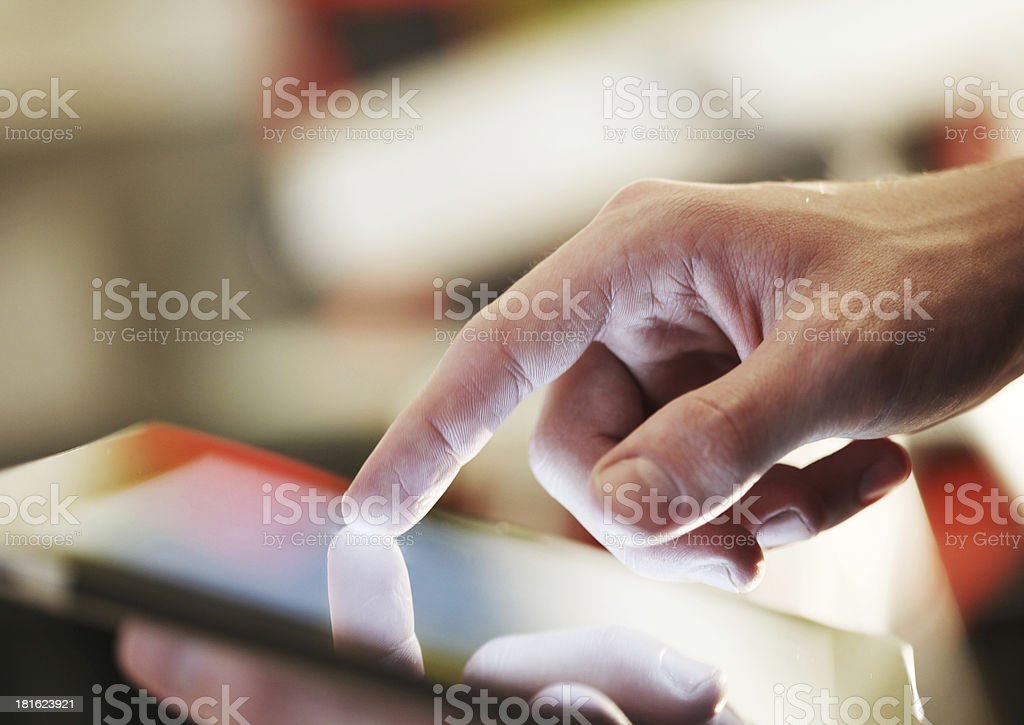 Close up of man's hand poring on tablet device royalty-free stock photo