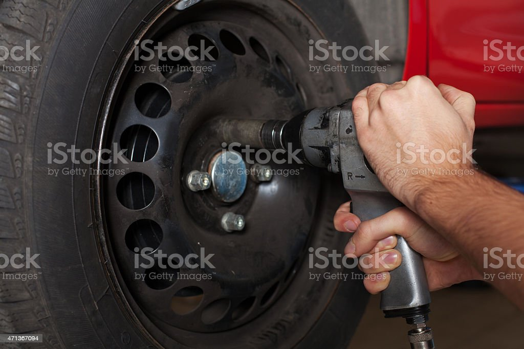 Close up of man's hands changing wheel. stock photo