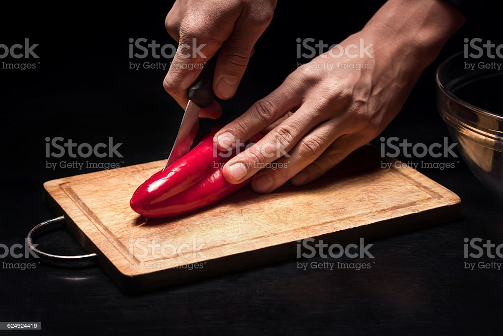 Close up of mans hands chopping bell pepper stock photo