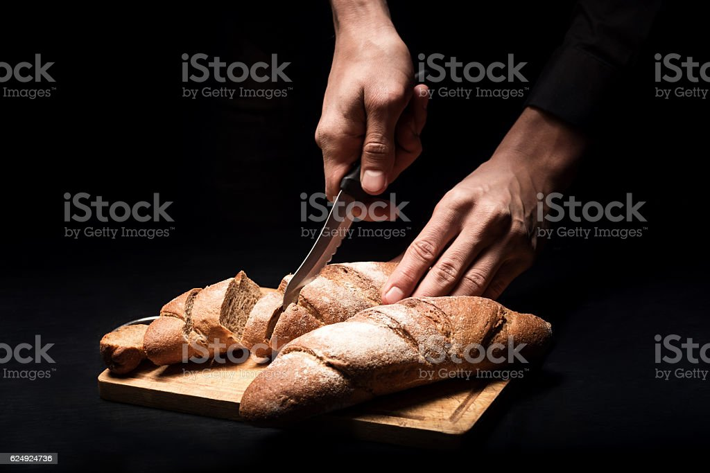 Close up of mans hands chopping the baguette stock photo