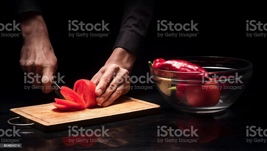 Close up of mans hands chopping tomato on black background stock photo