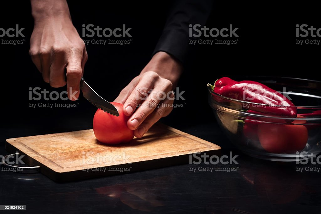 Close up of mans hands chopping tomato stock photo