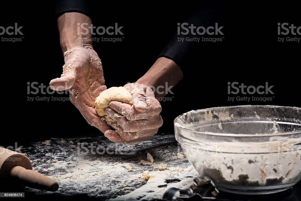 Close up of mans hands cooking bakery on black background stock photo