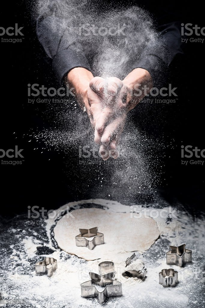 Close up of mans hands cooking cookies on black background stock photo