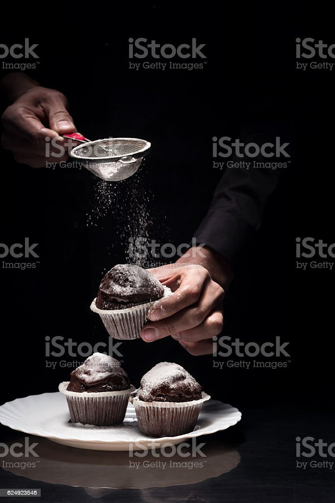 Close up of mans hands cooking the cupcakes stock photo