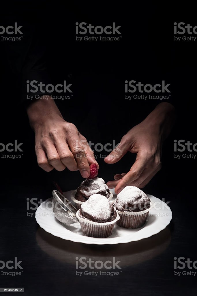 Close up of mans hands decorating cupcakes stock photo
