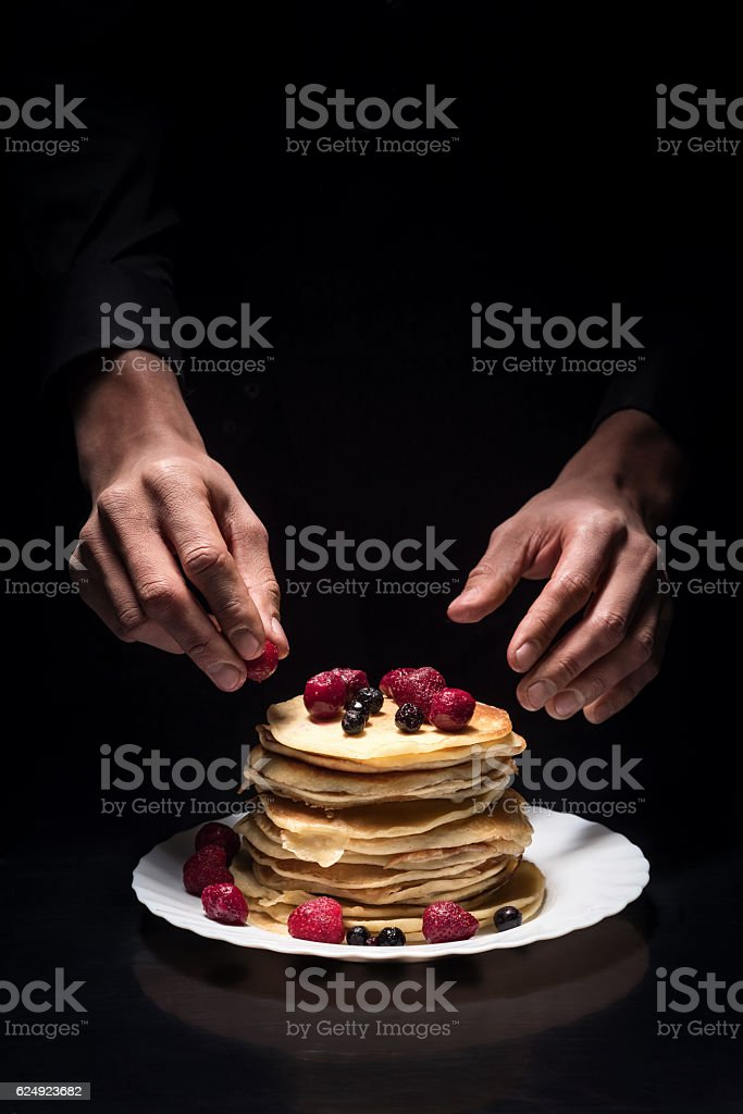 Close up of mans hands decorating the pancakes stock photo