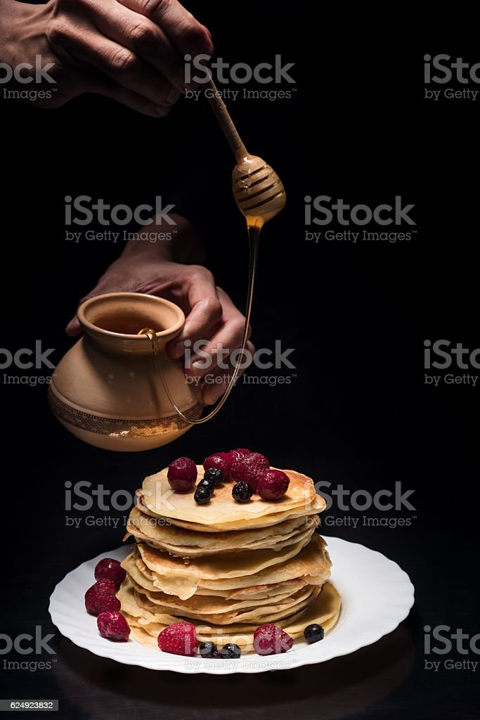 Close up of mans hands flavoring pancakes stock photo