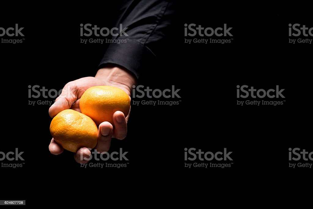 Close up of mans hands holding tangerines stock photo