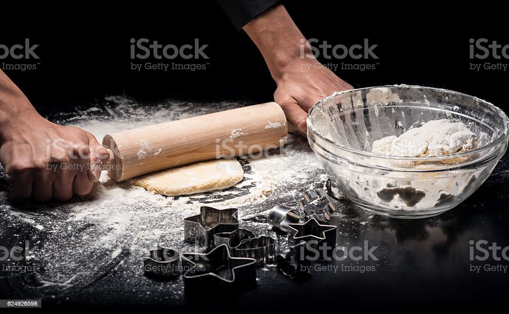 Close up of mans hands kneading dough with rolling pin stock photo