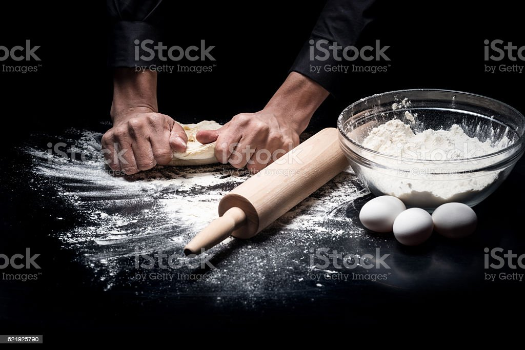 Close up of mans hands kneading the dough stock photo