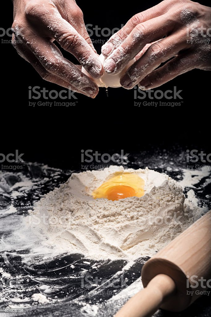 Close up of mans hands using eggs for a dough stock photo