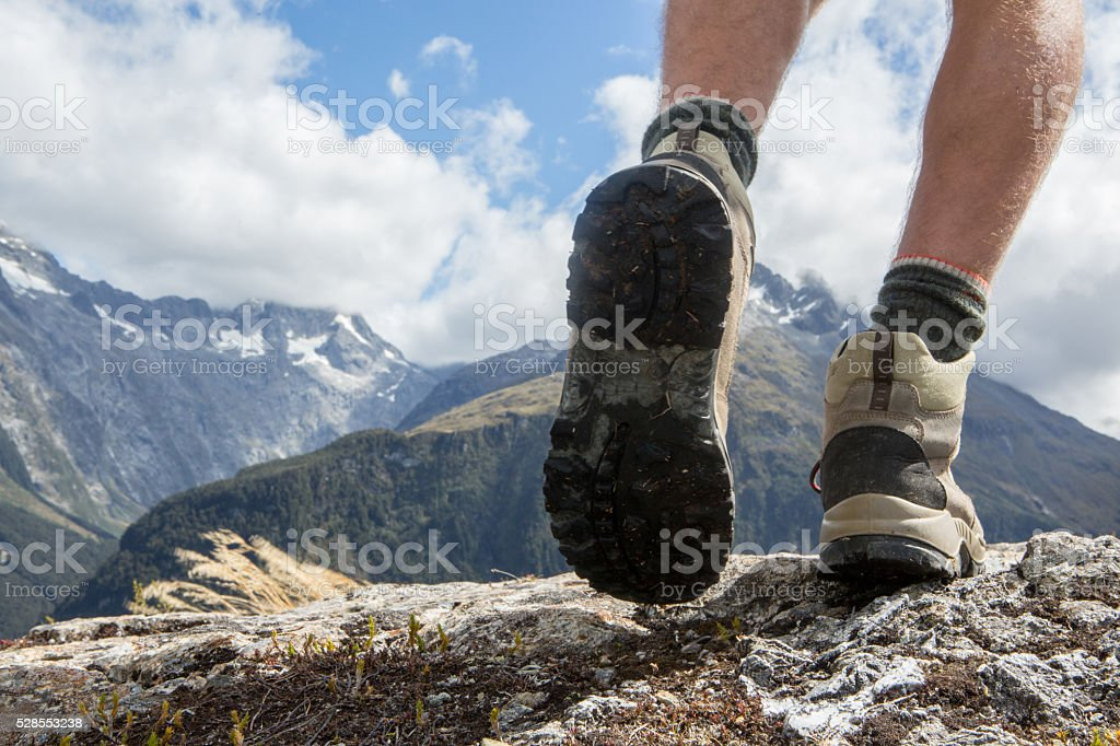 Close up of man's hiking boots on mountain trail stock photo