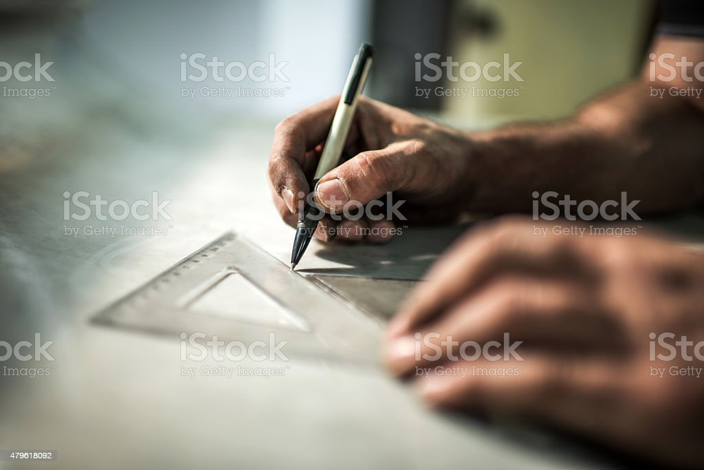 Close up of manual worker drawing a construction plan. stock photo