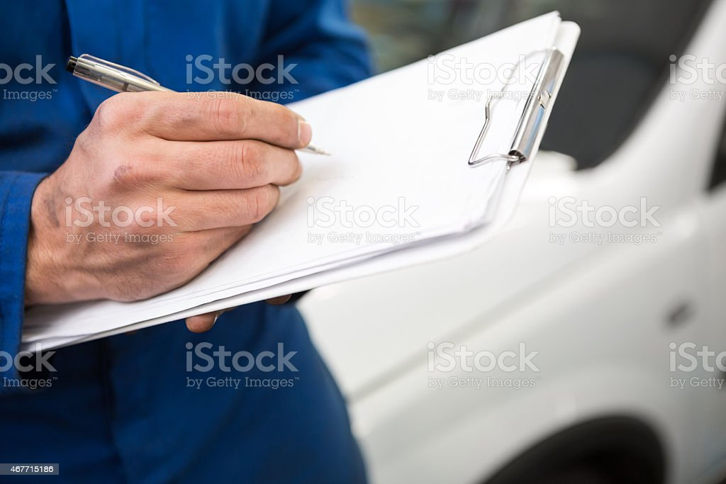 Close up of mechanic writing on clipboard stock photo