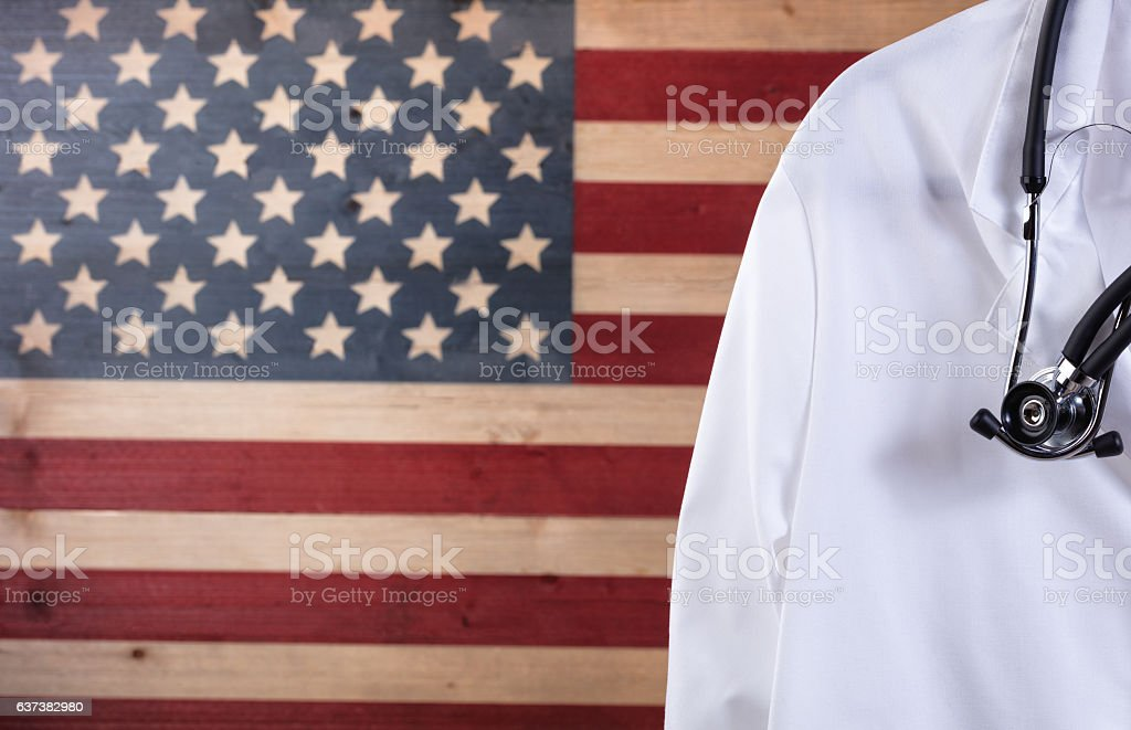 Close up of medical doctor jacket and stethoscope with flag stock photo