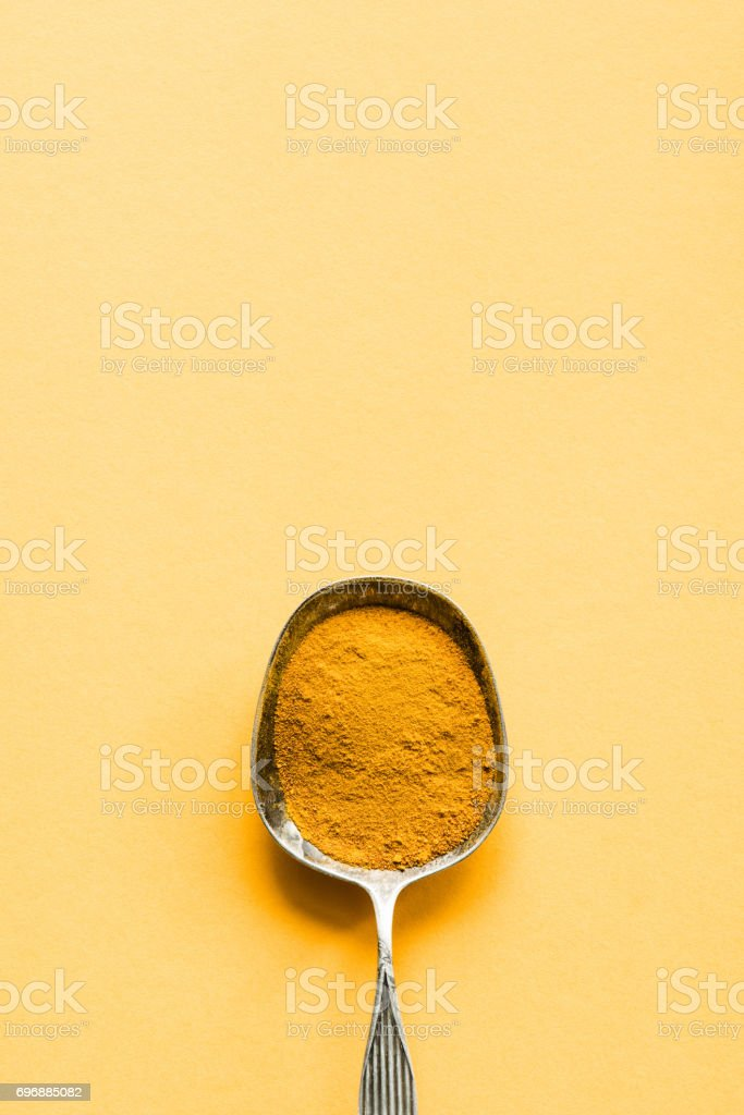 close up of metal spoon with curry powder on yellow surface stock photo