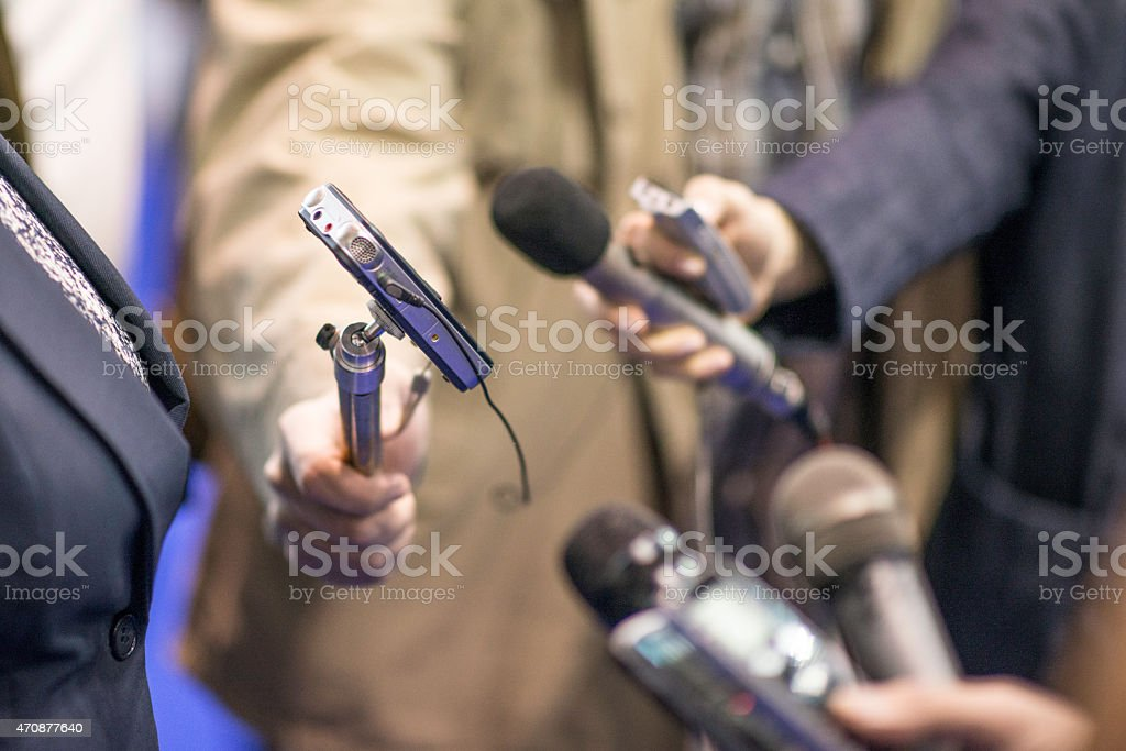 Close up of microphones and recorders held out for interview stock photo