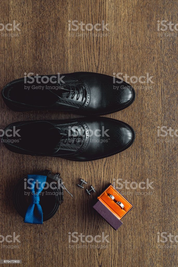 Close up of modern man accessories. Blue bowtie, leather shoes, belt,...