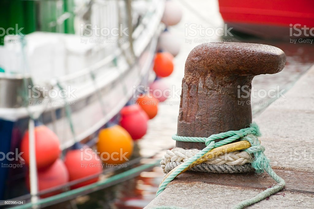 Close up of mooring post, multicolored ropes and buoys. stock photo
