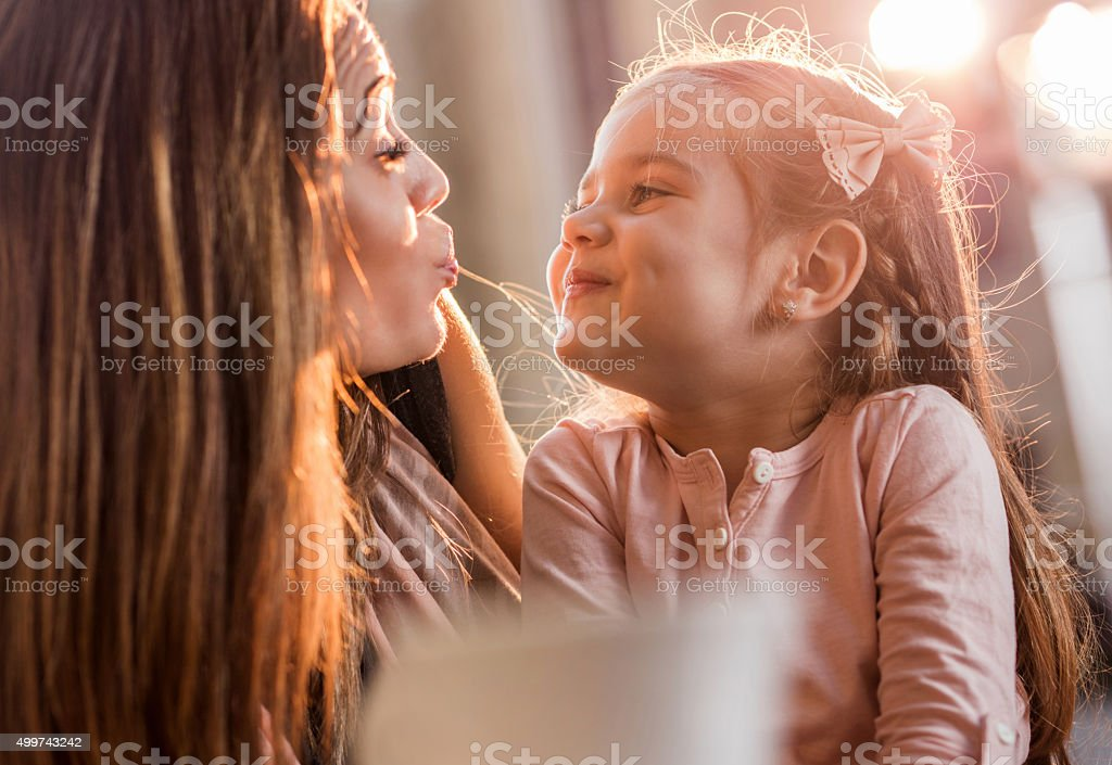 Close up of mother and daughter puckering to each other. stock photo