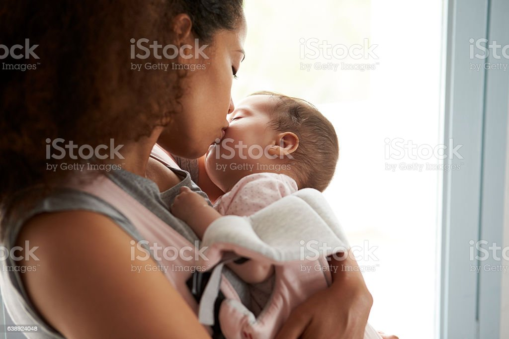 Close Up Of Mother Cuddling Baby Daughter At Home stock photo