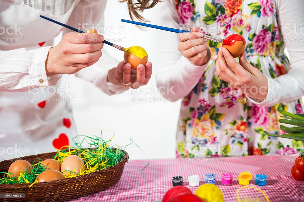 Close up of mother with daughter coloring eggs for Easter. stock photo