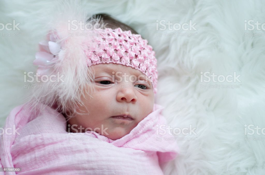 Close up of newborn baby girl in pink stock photo
