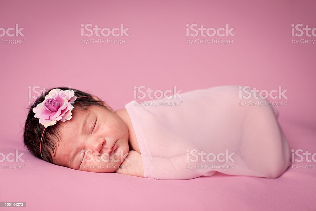 Close Up of Newborn Girl Wrapped in Sheer Fabric stock photo