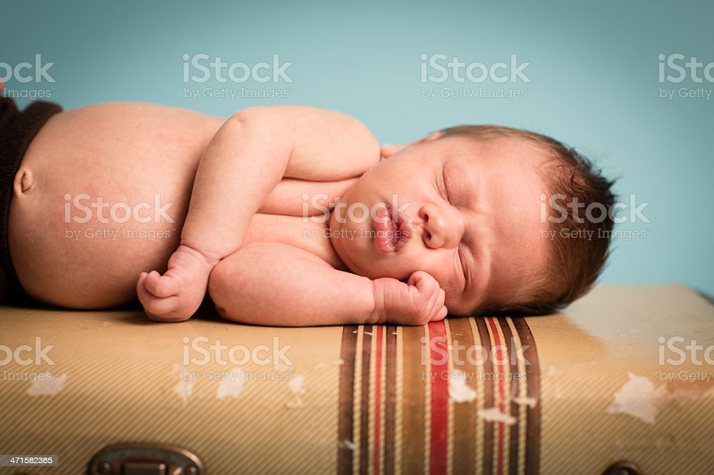 Close Up of Newborn Lying on Vintage, Striped Suitcase royalty-free stock photo