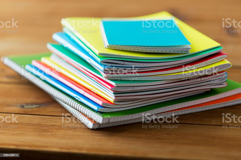 close up of notebooks on wooden table stock photo