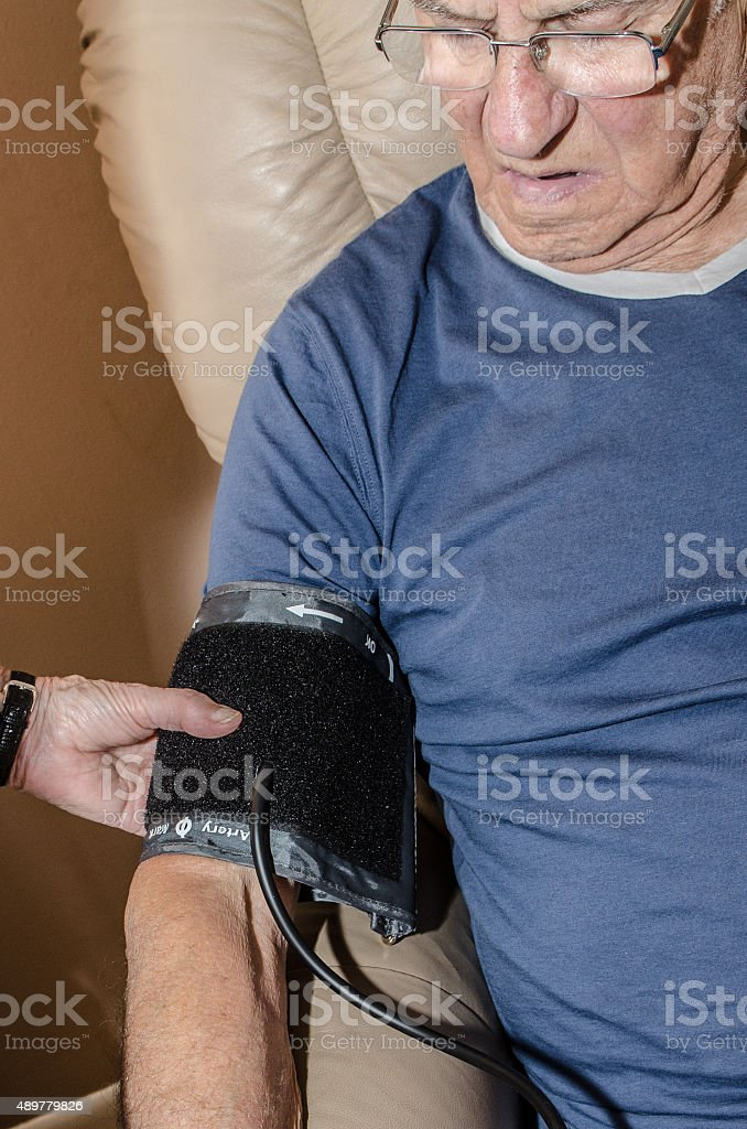 Close up of old man's arm  while taking blood pressure stock photo