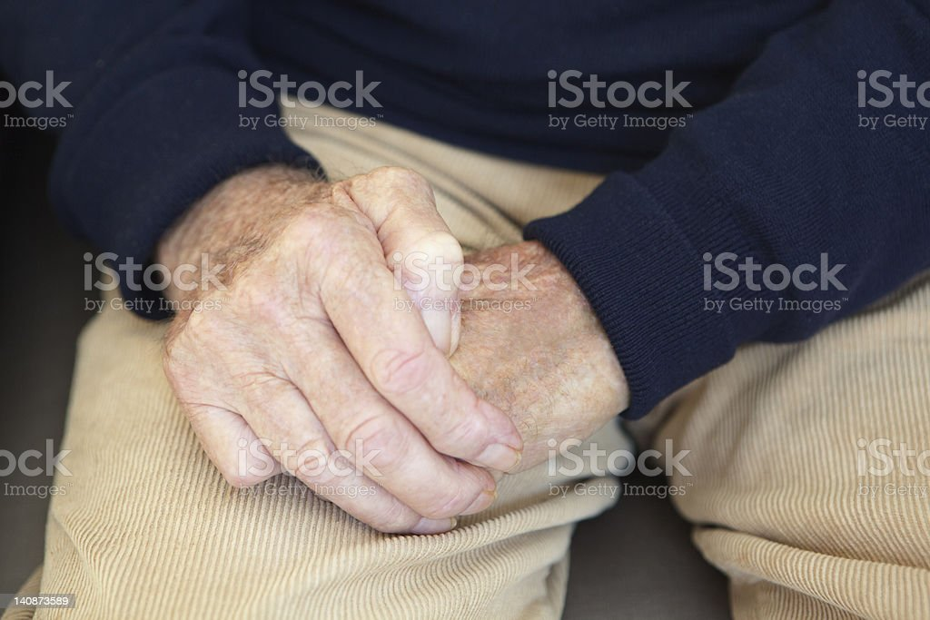 Close up of older mans folded hands stock photo
