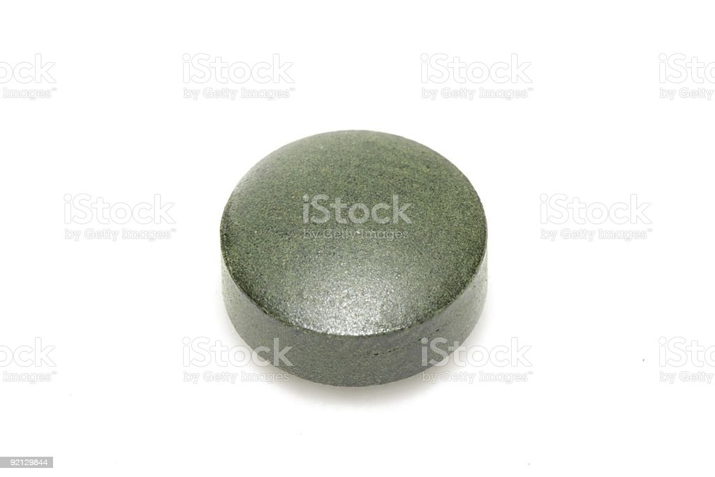Close up of one spirulina tablet royalty-free stock photo