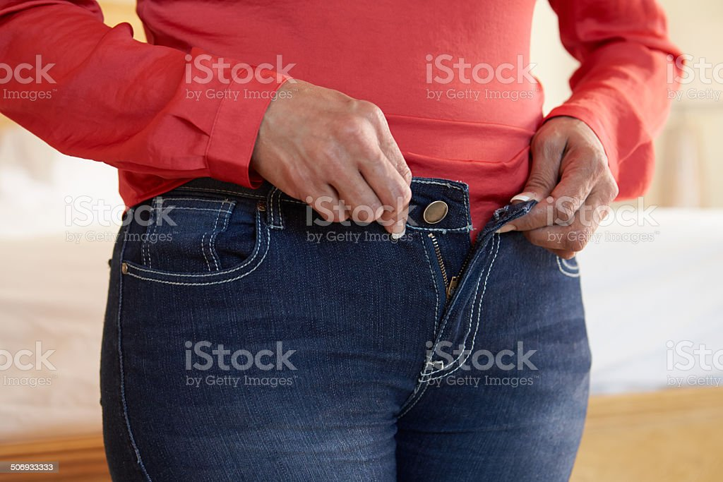 Close Up Of Overweight Woman Trying To Fasten Trousers stock photo
