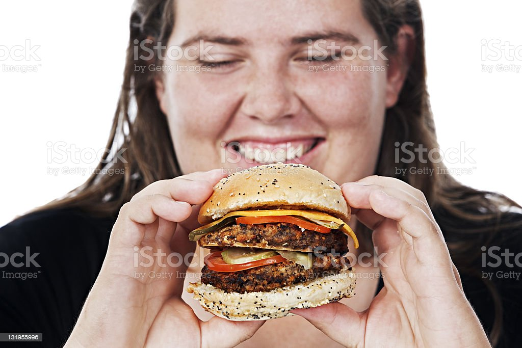 Close up of overweight young woman lovingly eyeing juicy burger stock photo