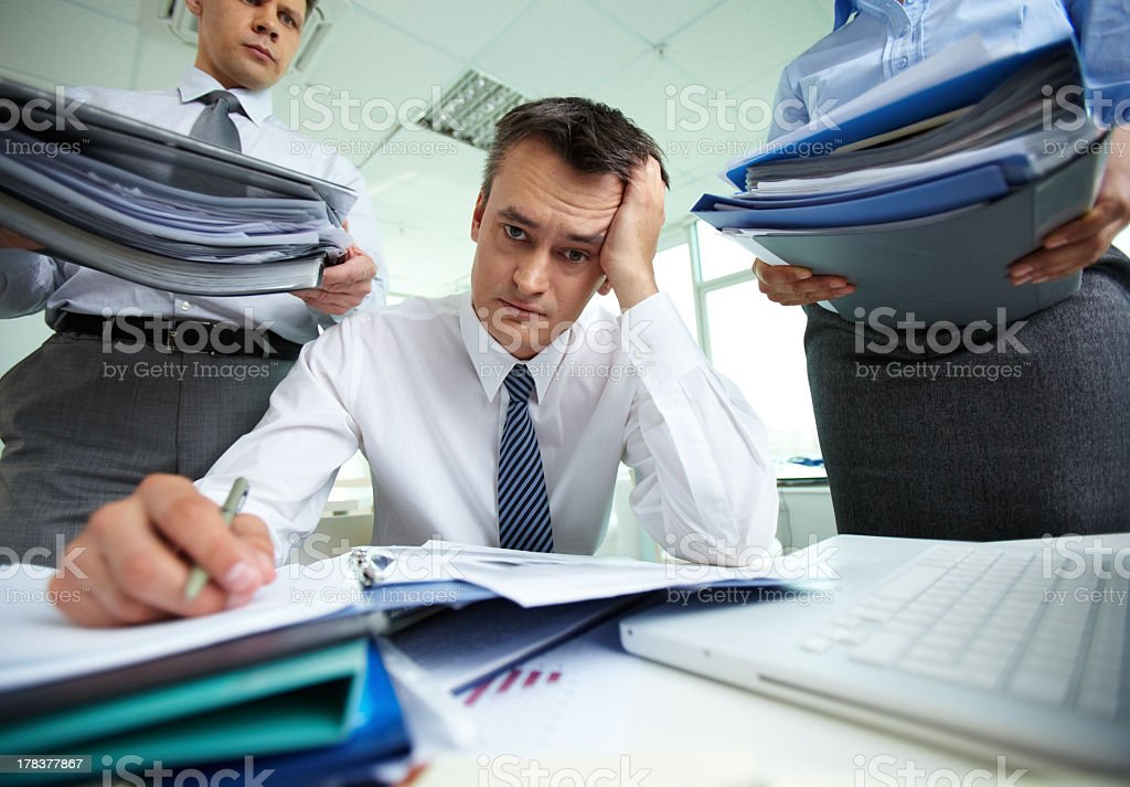 Close up of over-worked man in office surrounded by papers stock photo