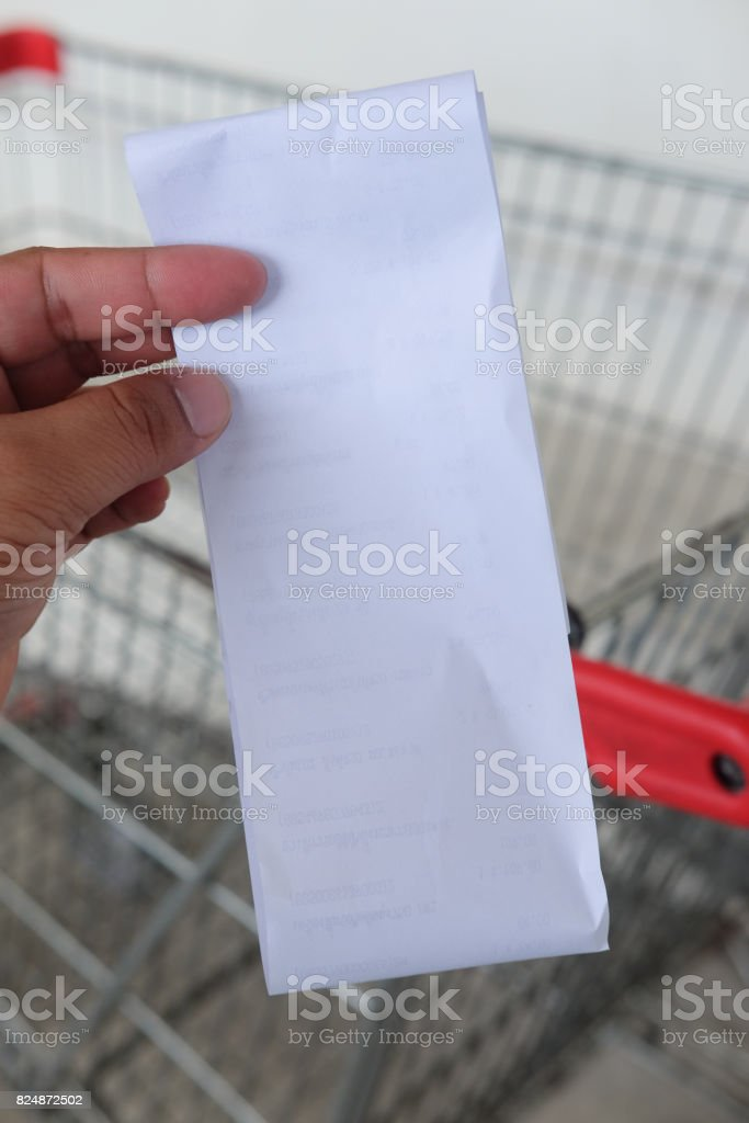 Close up of paper receipt bill in human hand  (Supermarket shop) stock photo