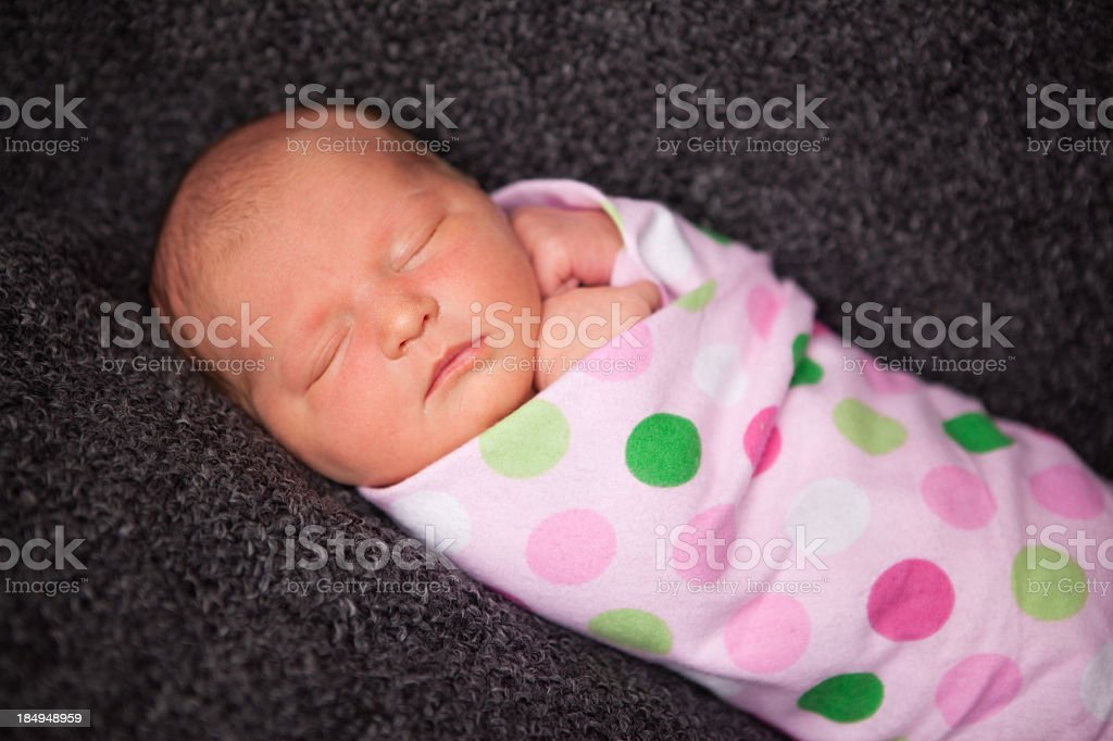 Close Up of Peaceful Newborn Baby Girl Swaddled in Blanket stock photo