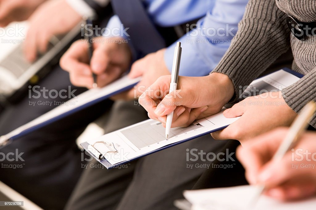 A close up of people writing notes royalty-free stock photo
