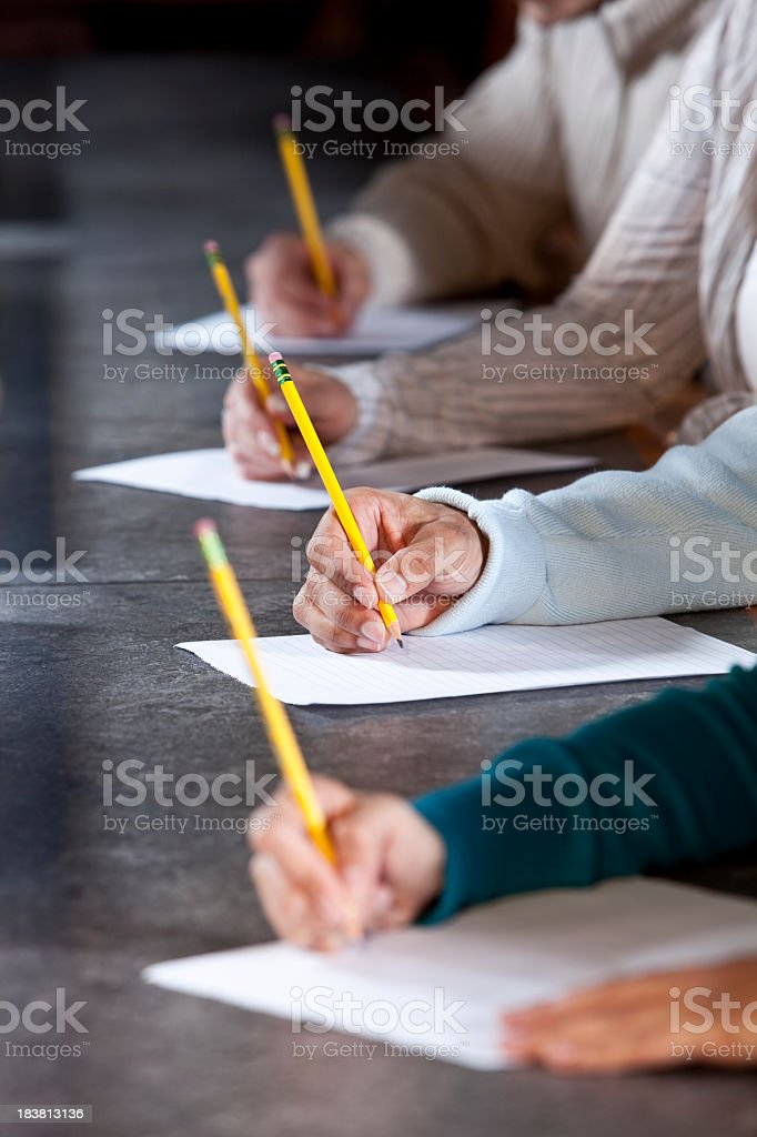 Close up of people writing with pencils stock photo