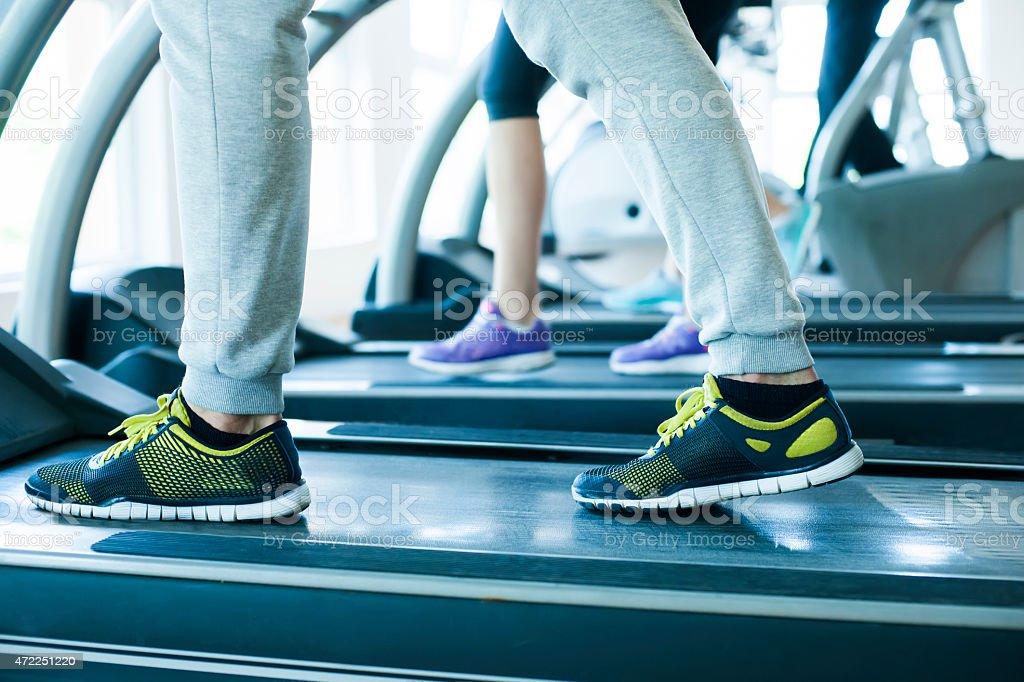 Close up of people's legs running on treadmill stock photo