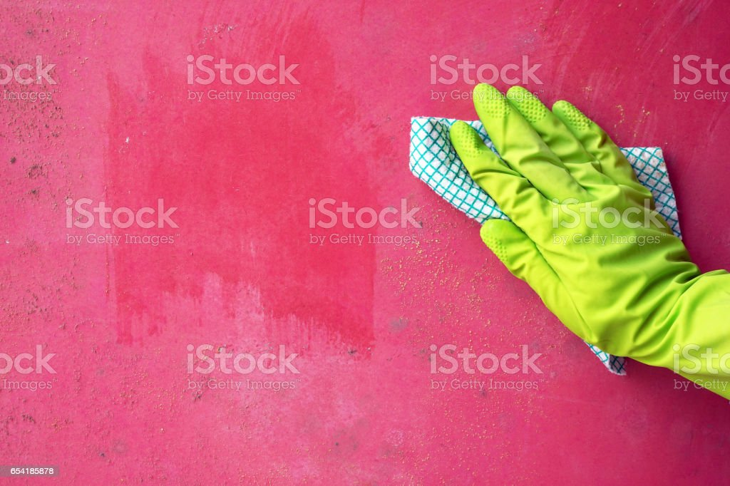 Close up of person hand cleaning mold fungus from wall using rag stock photo