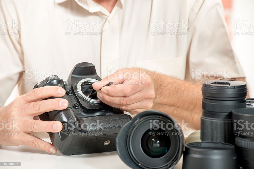 Close up of photographer hand cleaning sensor of his camera stock photo